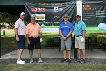 four golfers standing with sponsorship banner