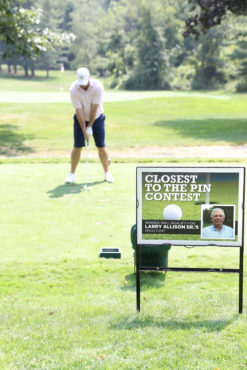 golfer taking a put with closest to the pin sign